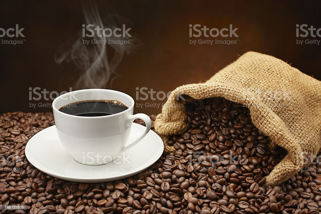 Steaming cup of coffee on pile of coffee beans stock photo