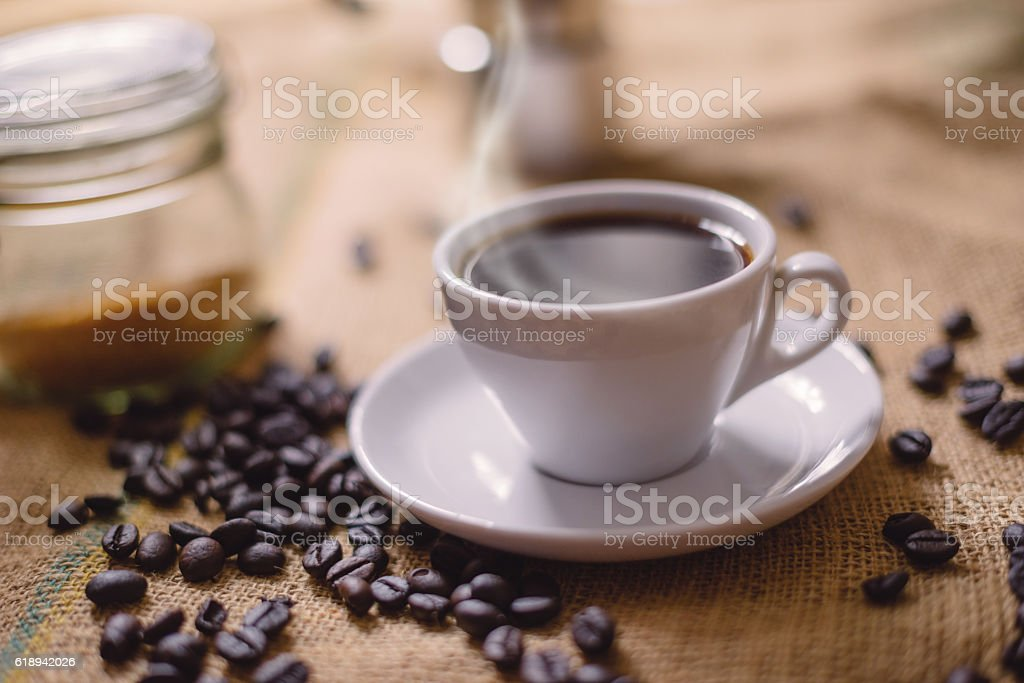 Steaming cup of coffee with coffee beans stock photo
