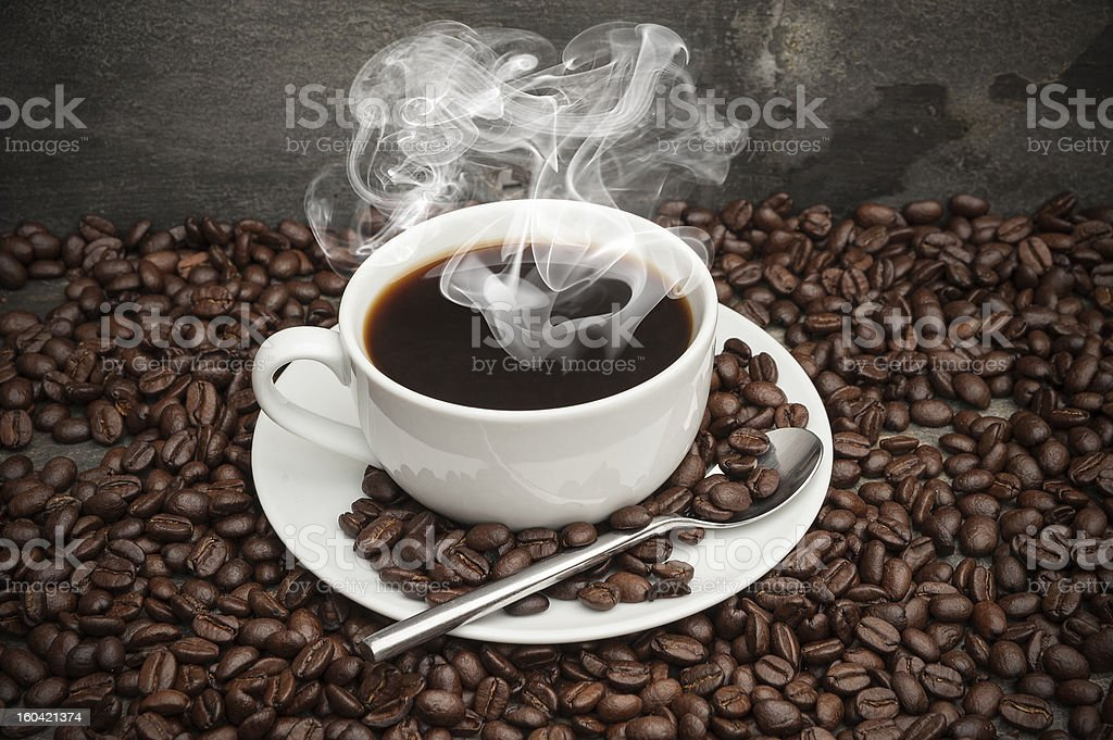 Steaming hot cup of coffee surrounded by beans royalty-free stock photo