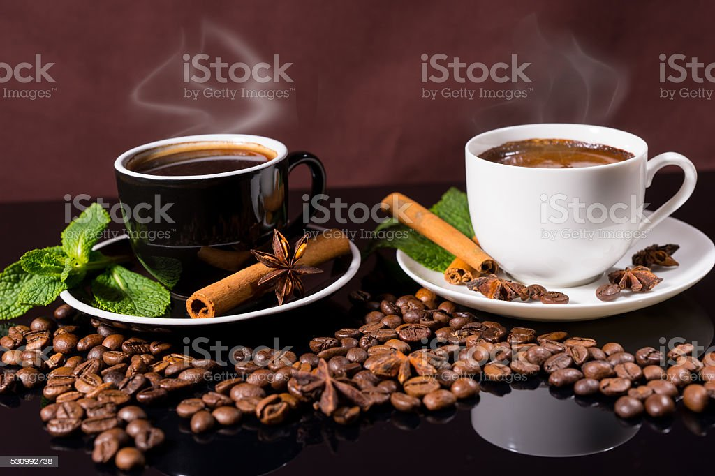 Steaming Hot Cups of Coffee with Roasted Beans stock photo