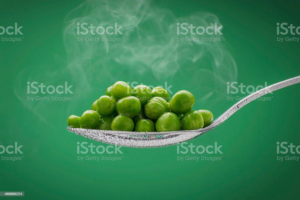 Fumegante da ervilha em uma colher foto royalty-free
