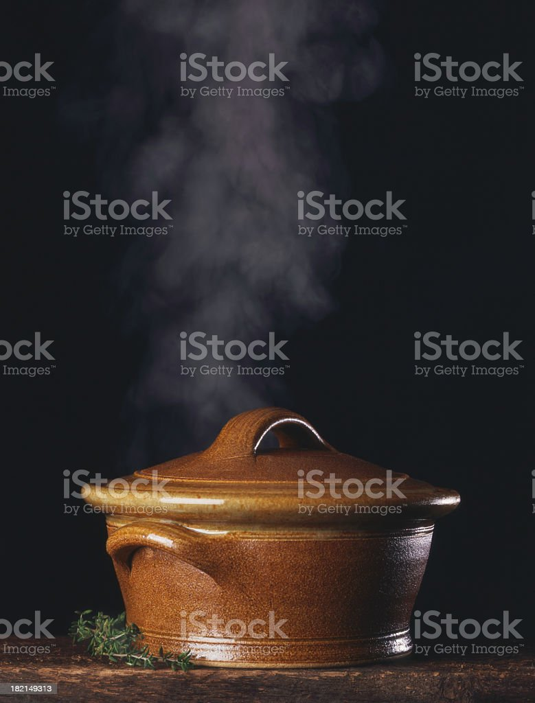Steaming stock pot isolated on black on rustic wood table  stock photo