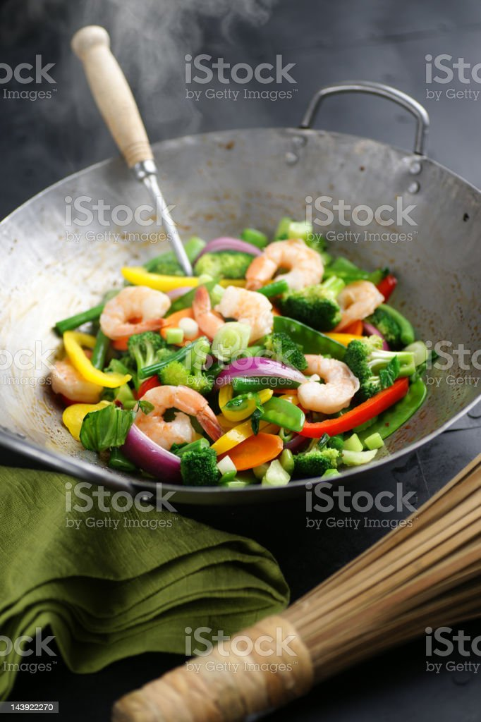 A steaming wok filled with shrimp stir fry with vegetables stock photo