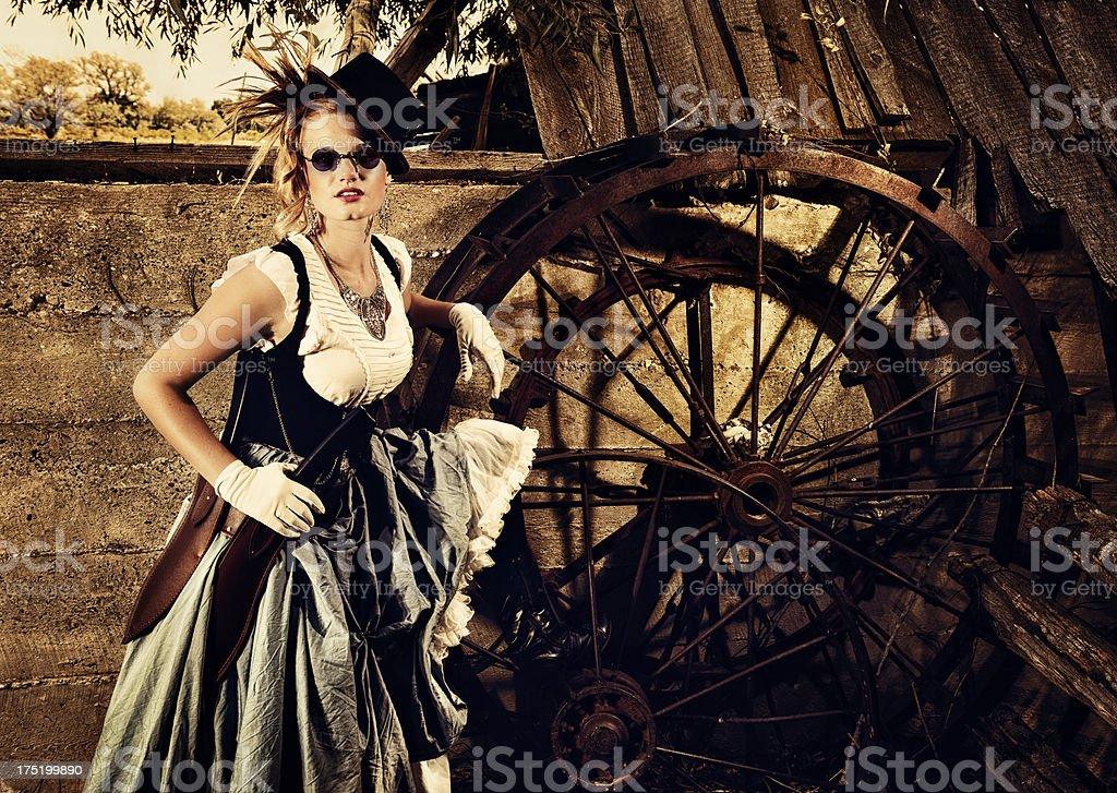 Steampunk Double Machete Wielding Woman Near Giant Metal Spoked Wheel stock photo
