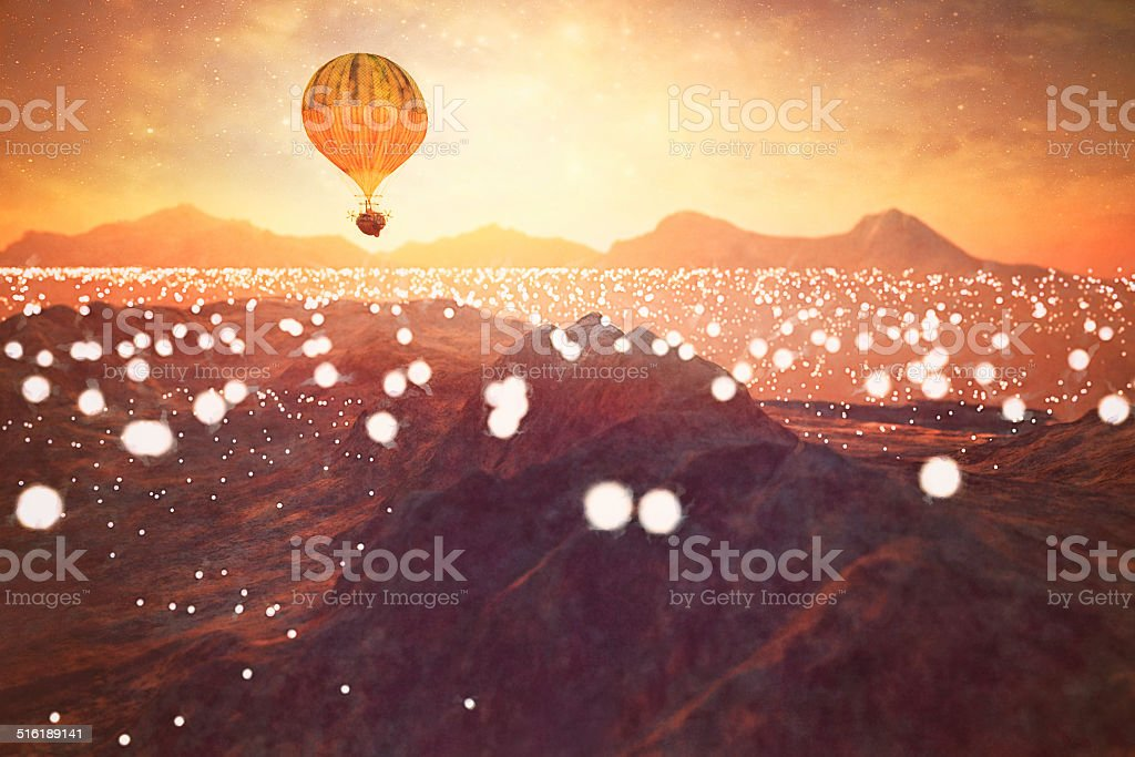 Steampunk hot air ballon flying over illuminated fantasy landscape stock photo