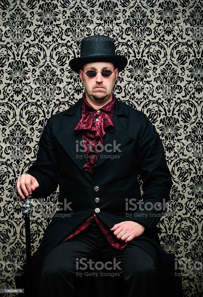 Steampunk Man Sitting Against Damask Background stock photo