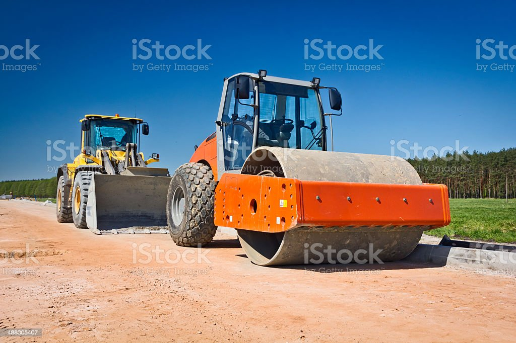 Steamroller and earth mover in road construction stock photo