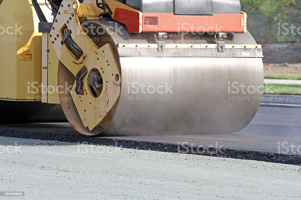 Steamroller Compressing Hot Asphalt On A New Road Paving Project stock photo