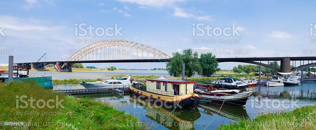 steel arch bridge with small harbor stock photo