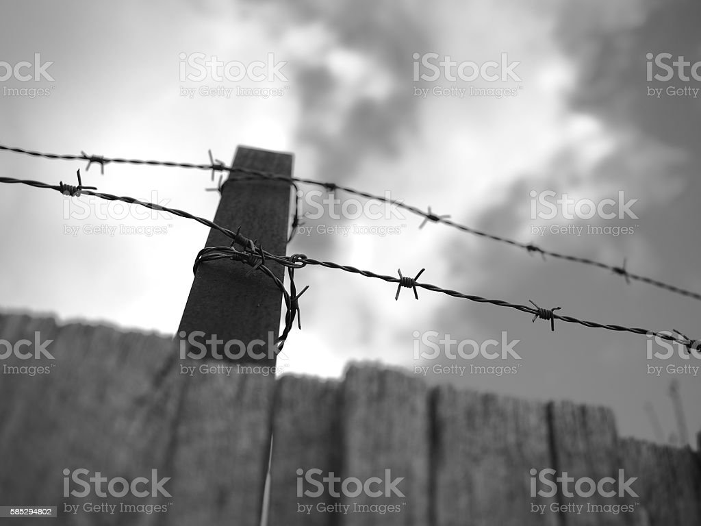 Steel barb wire on a fence under cloudy sky stock photo