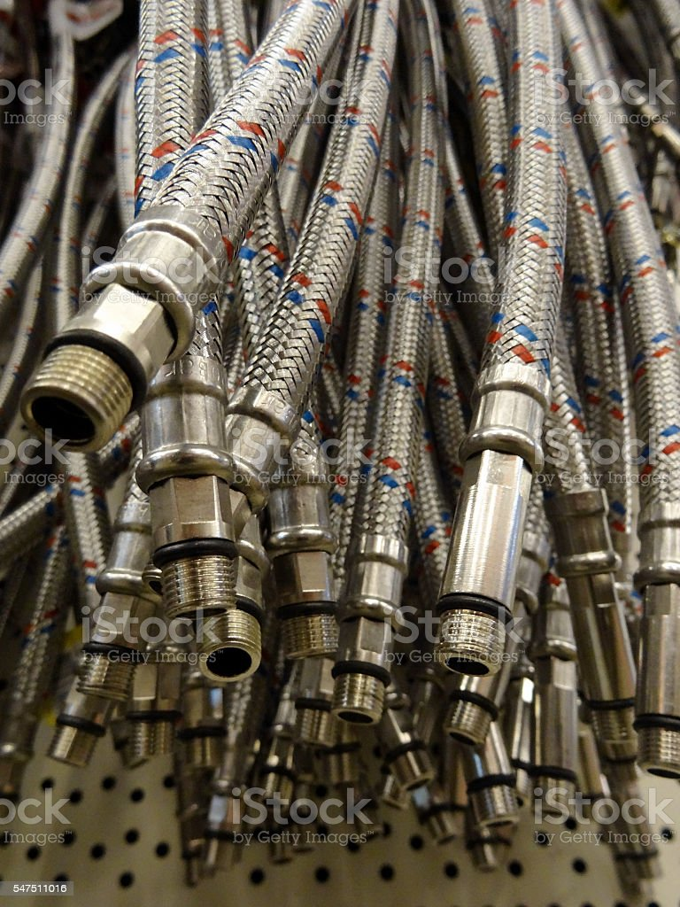 Steel braid hoses hanging on the shelf at the sanitary shop stock photo