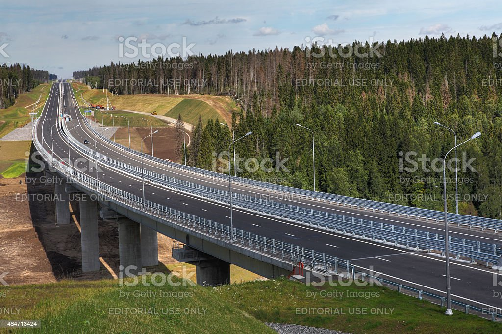 Steel bridge over river forest, concrete pillars supporting metal structures. stock photo