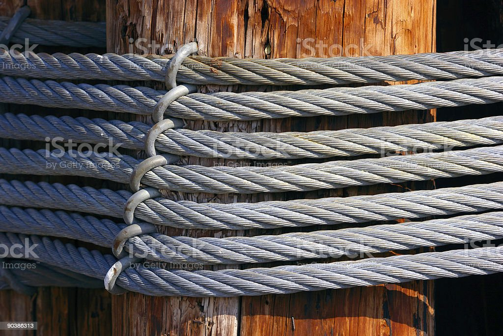 Steel cables twisted over wooden pile royalty-free stock photo