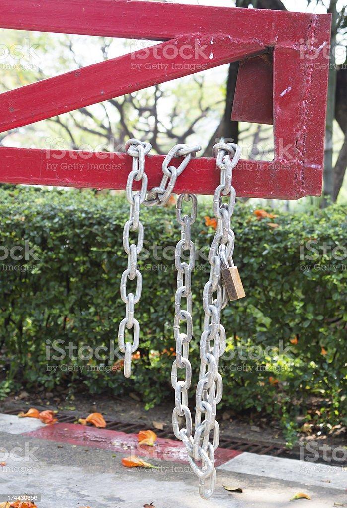 Сталь-цепочка через плечо с замком защелкой на красном Дорожный барьер Стоковые фото Стоковая фотография