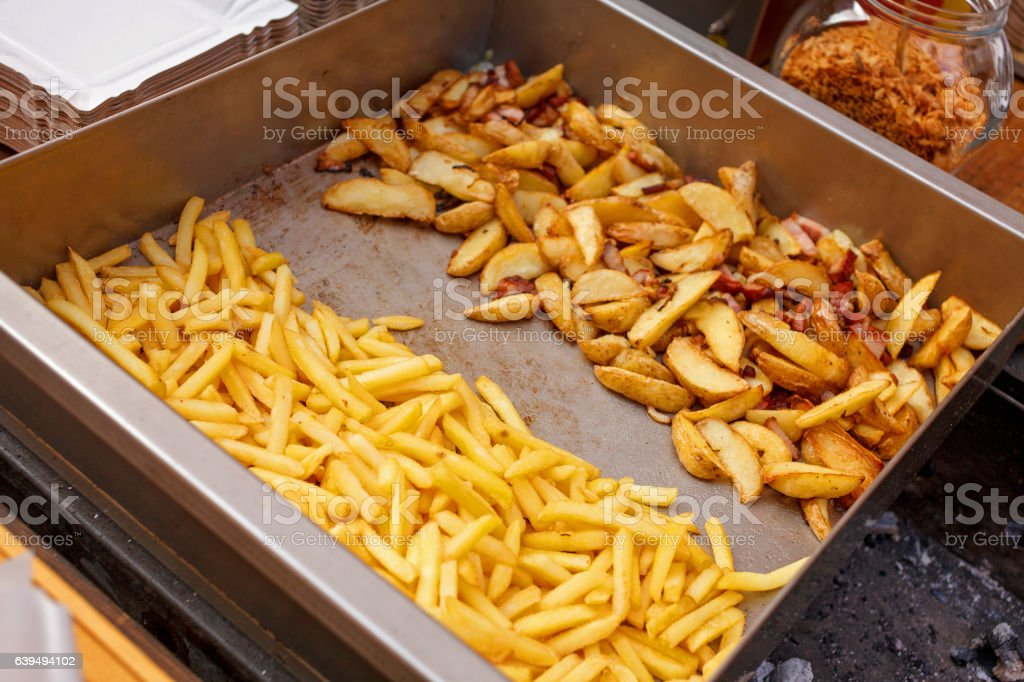 Steel container with roasted potato wedges, french fries stock photo