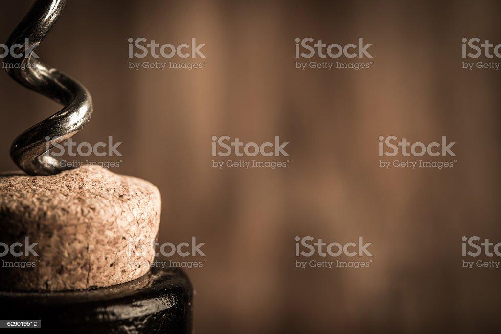 Steel corkscrew opens a bottle of wine closeup stock photo