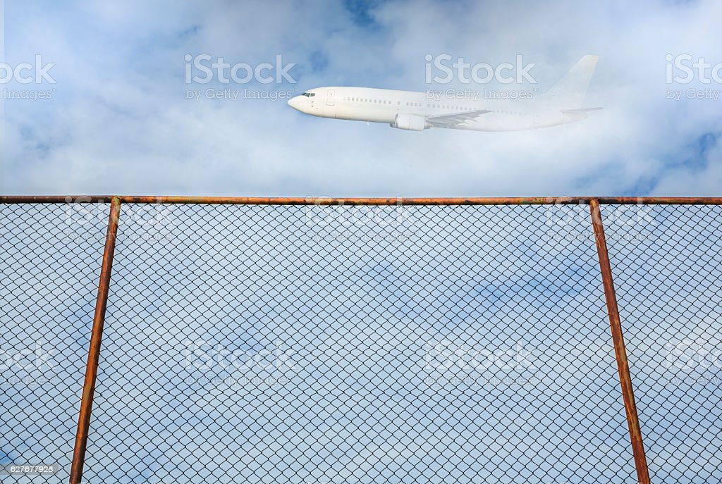 steel fence with plane flying in the sky stock photo