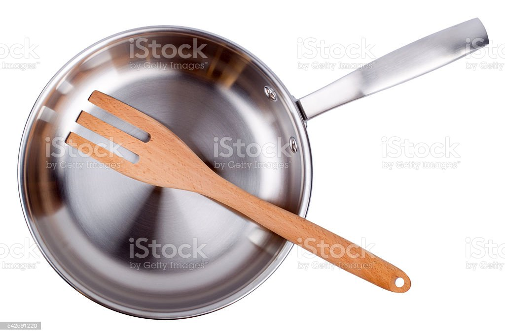 Steel frying pan and wooden scapula isolated on a white stock photo