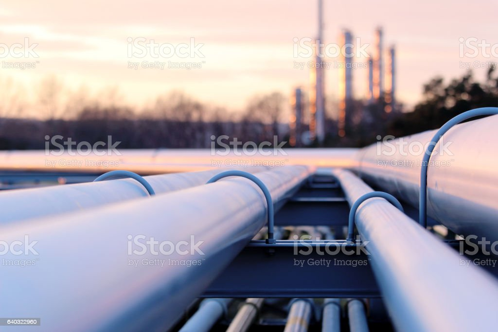steel long pipes in crude oil factory during sunset stock photo