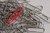 Steel paper clips with a single red paperclip
