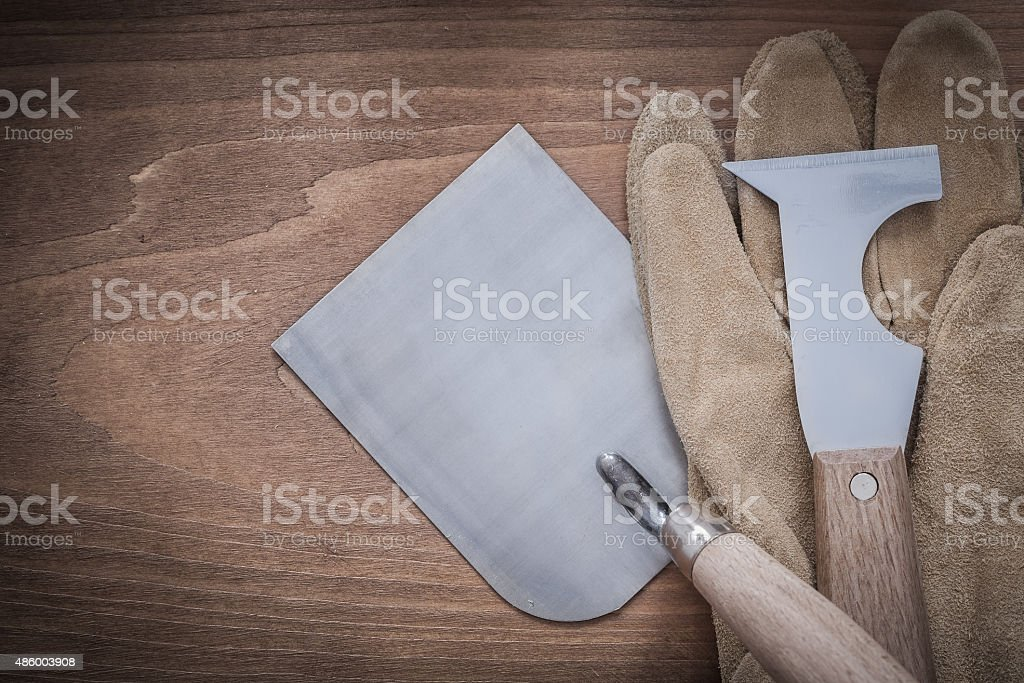 Steel putty knife bricklaying trowel and leather protective glov stock photo