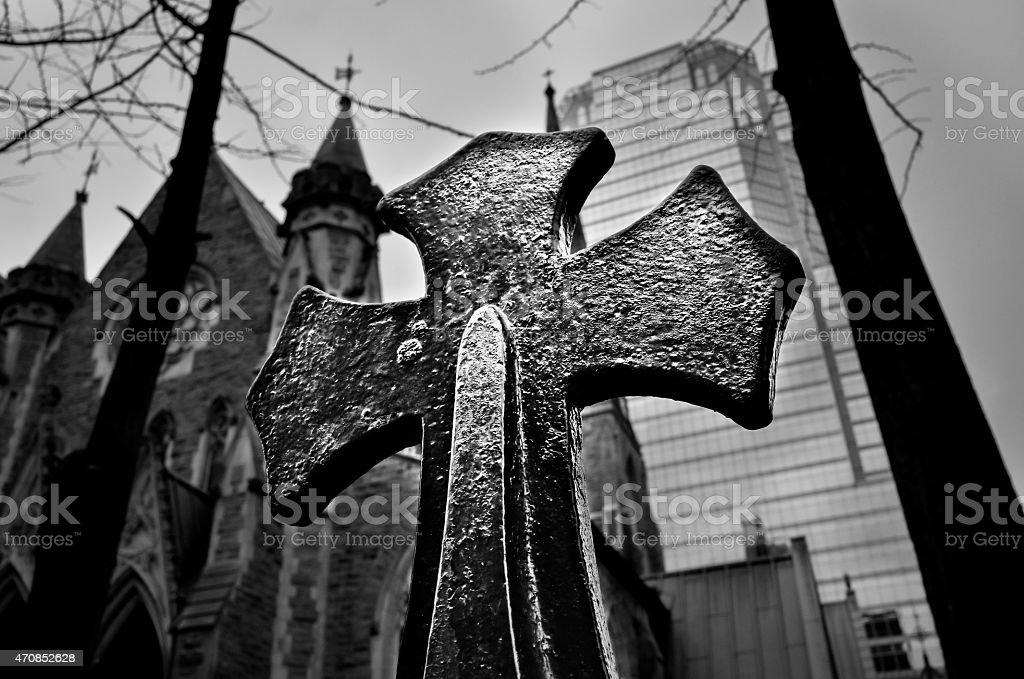 Steel religious cross on skyscraper background black and white stock photo
