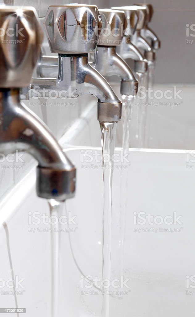 steel taps with drinking water flowing in college bathroom stock photo