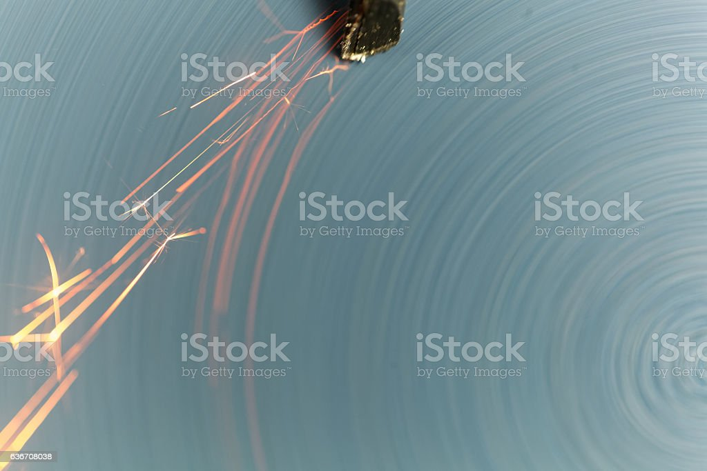 Steel tool on a grinder with sparks stock photo