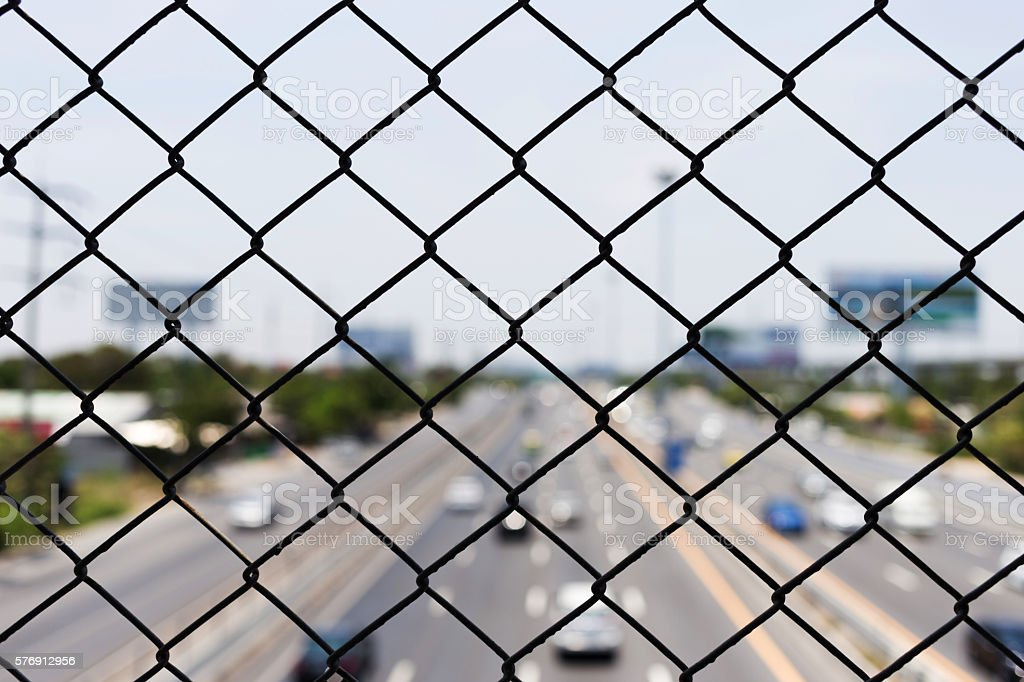 steel wire mesh (mesh fence) with city road highway stock photo