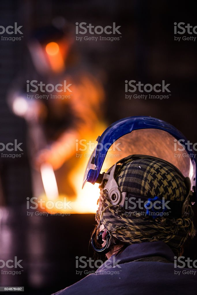 Steel worker in protective clothing raking furnace in an industr stock photo