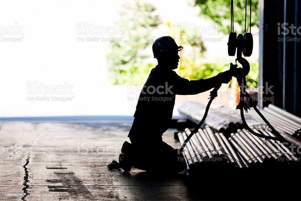 Steel worker tying metal tubes to crane jib in warehouse royalty-free stock photo