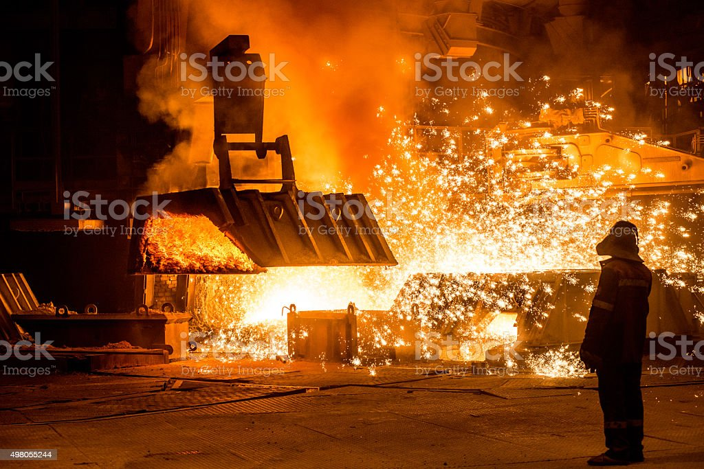 Steelworker near a blast furnace with sparks. stock photo