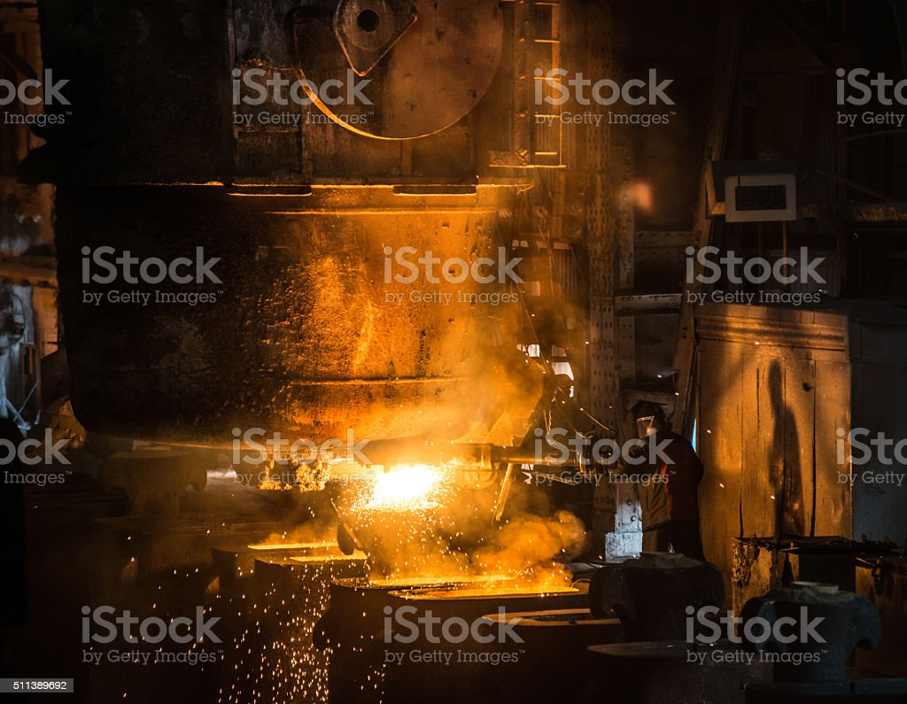 Steelworker pours liquid metal into molds from tank stock photo