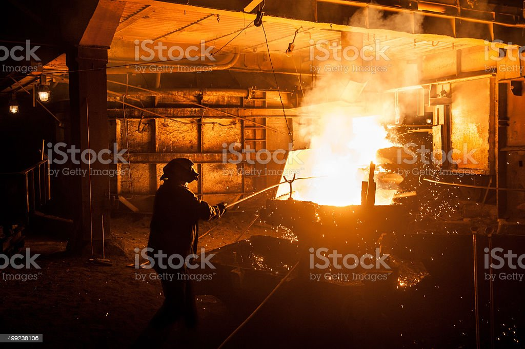 Steelworker when pouring liquid titanium slag from arc furnace stock photo