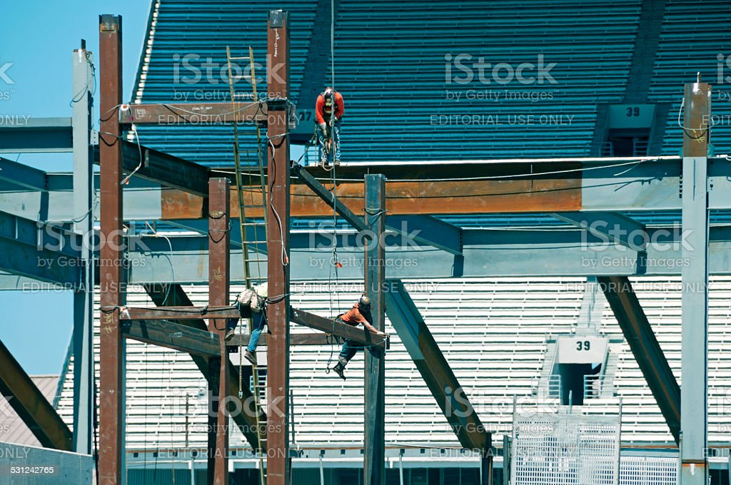 Steelworkers connecting girders on new stadium stock photo