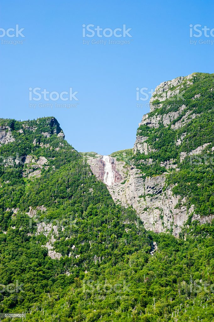 Steep cliffs covered in trees with distant waterfall under blue stock photo