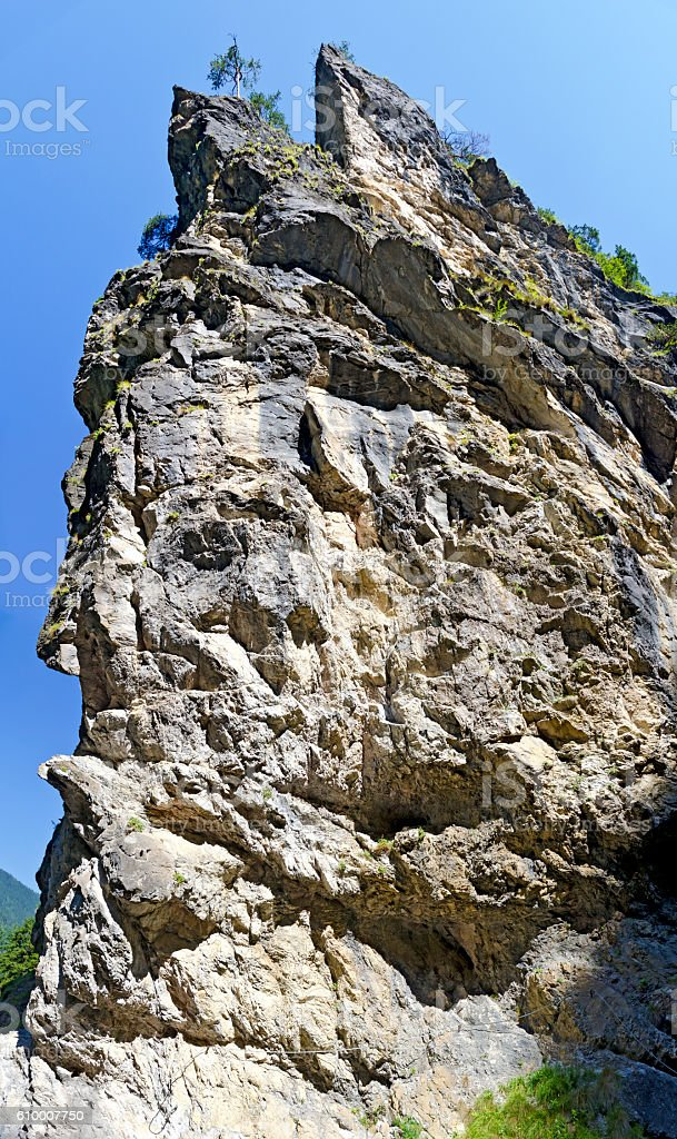steep rock face before blue sky stock photo