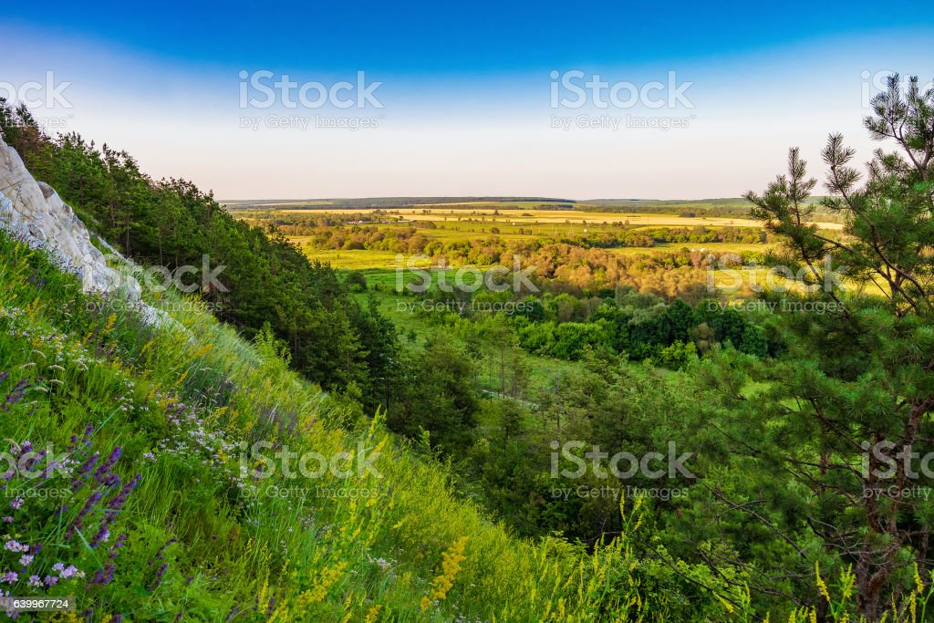 Steep slope of the chalk mountain overlooking the green plain stock photo