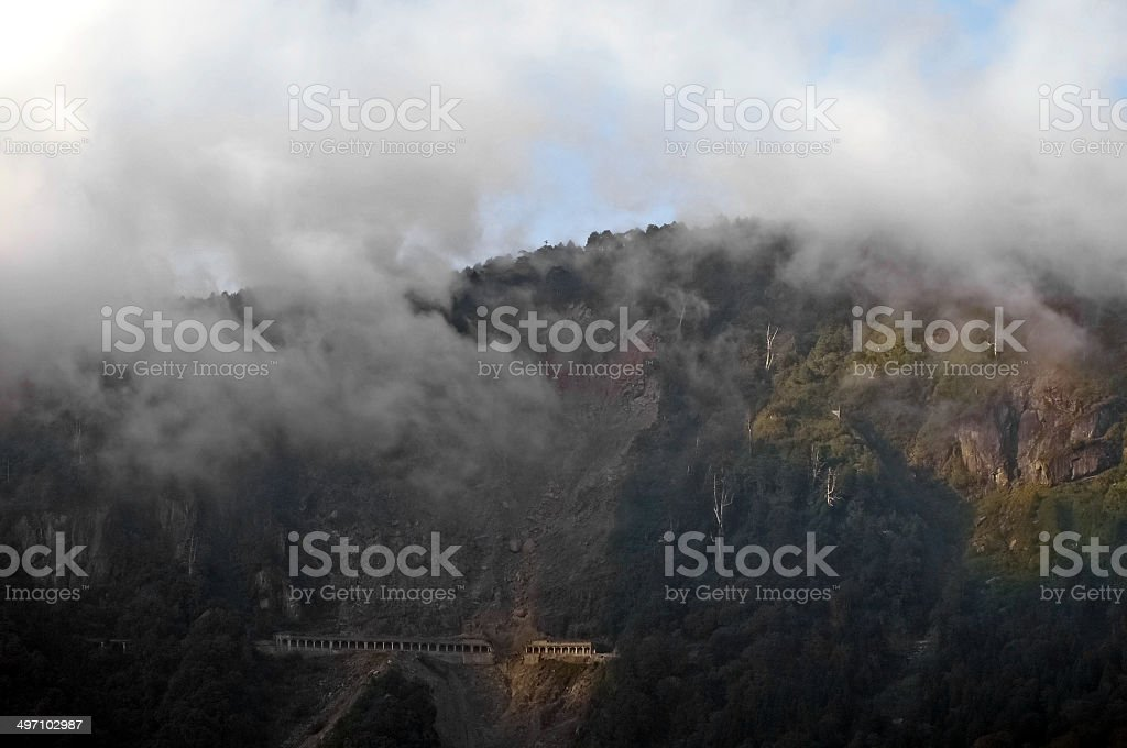 Steep tunnel on the peak of misty mountain stock photo