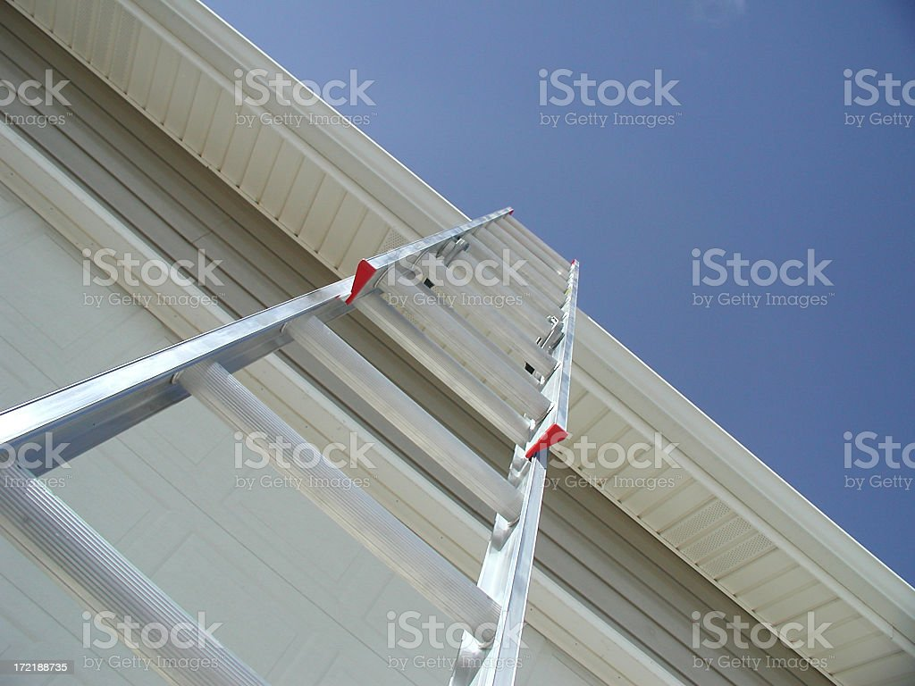 Steep Upward View of Aluminum Extension Ladder Against a Garage royalty-free stock photo