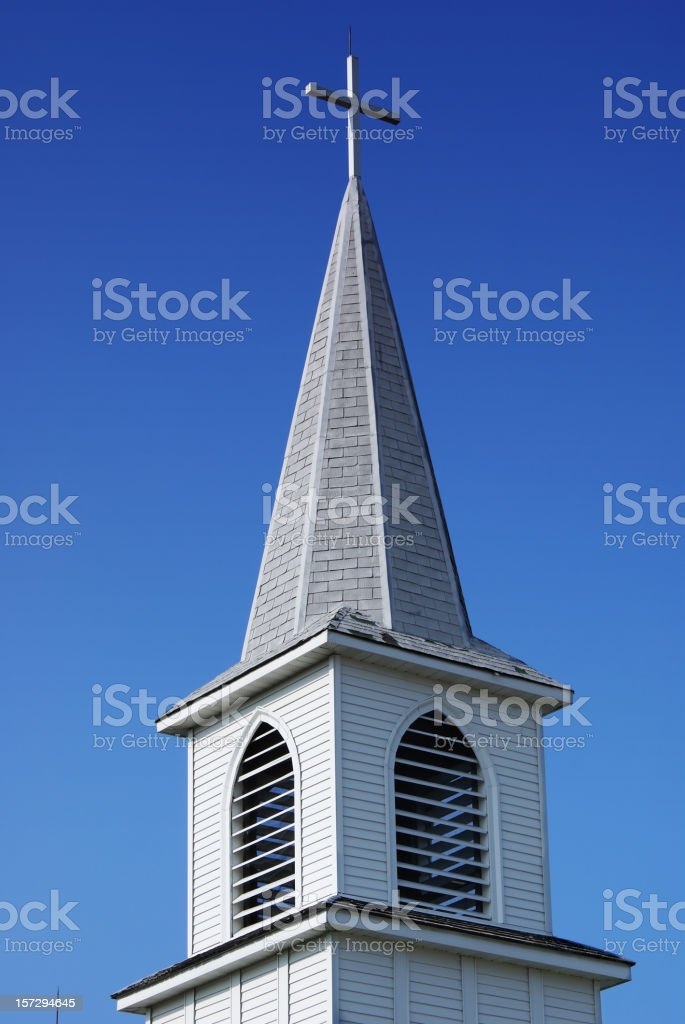 Steeple with a cross on an older white country church. stock photo