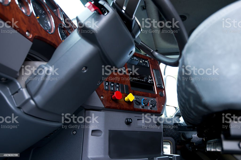Steering column and dashboard in cab of semi truck stock photo