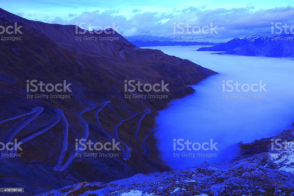 Stelvio pass landscape at dusk above mist, Italy stock photo