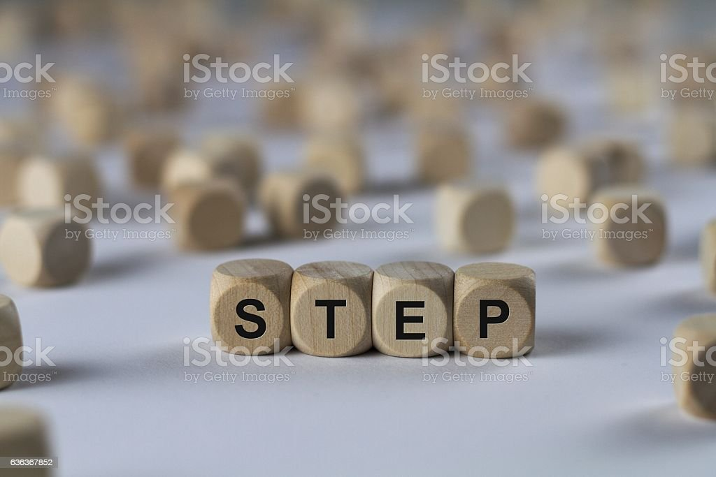 step - cube with letters, sign with wooden cubes stock photo