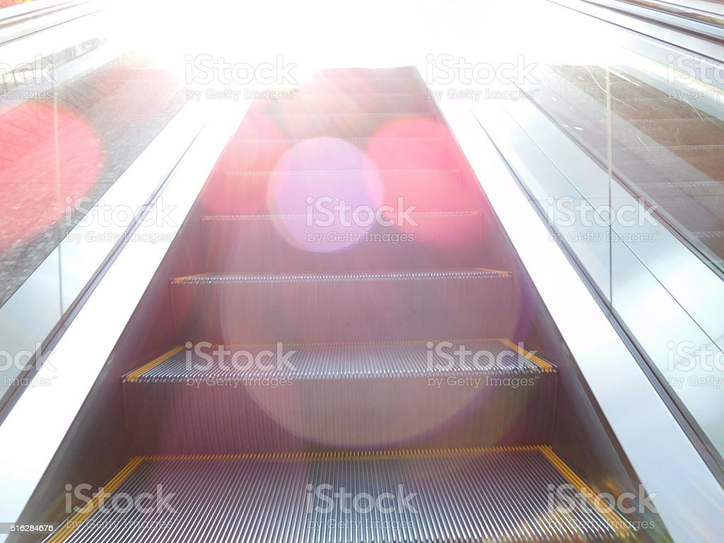 Step up to the light on an escalator stock photo