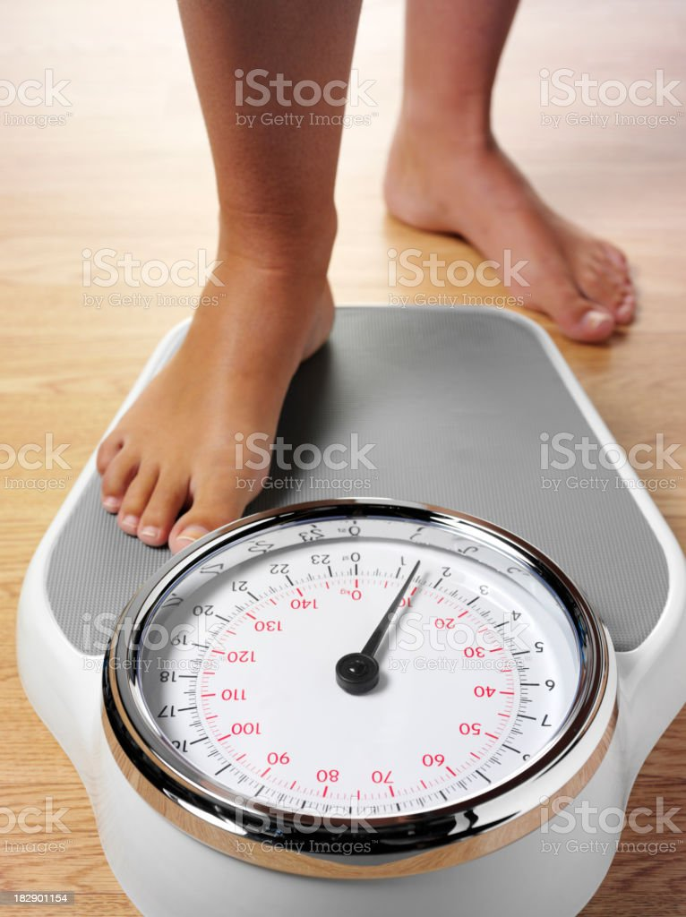 Stepping on Bathroom Scales stock photo