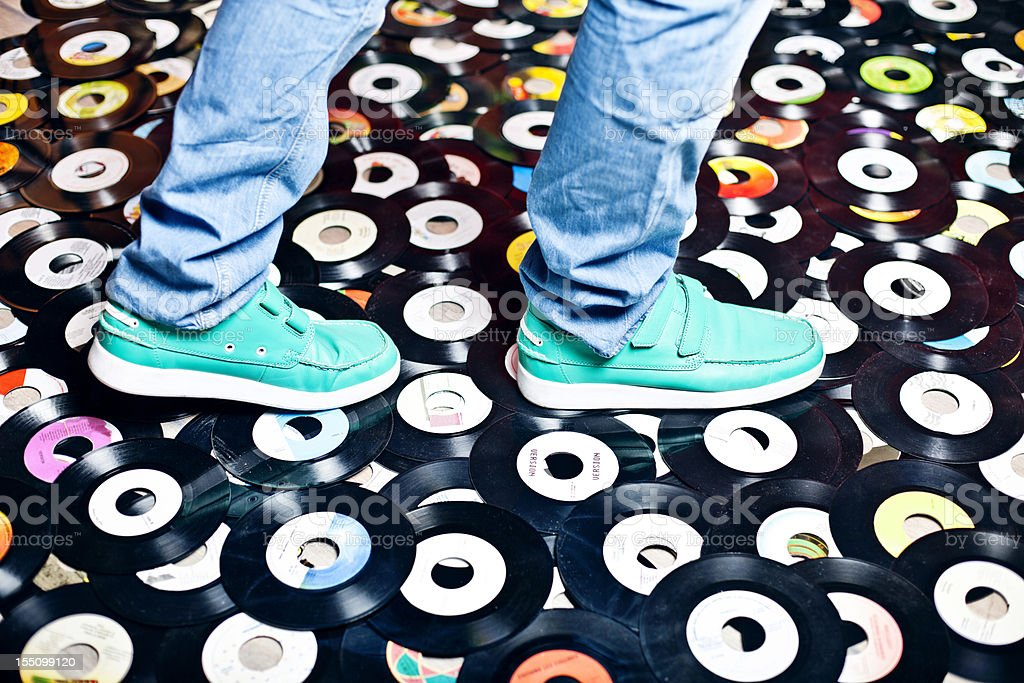 stepping on  vinyl records stock photo