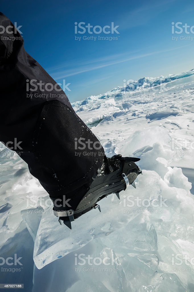 Stepping onto plate ice with boot cleats stock photo