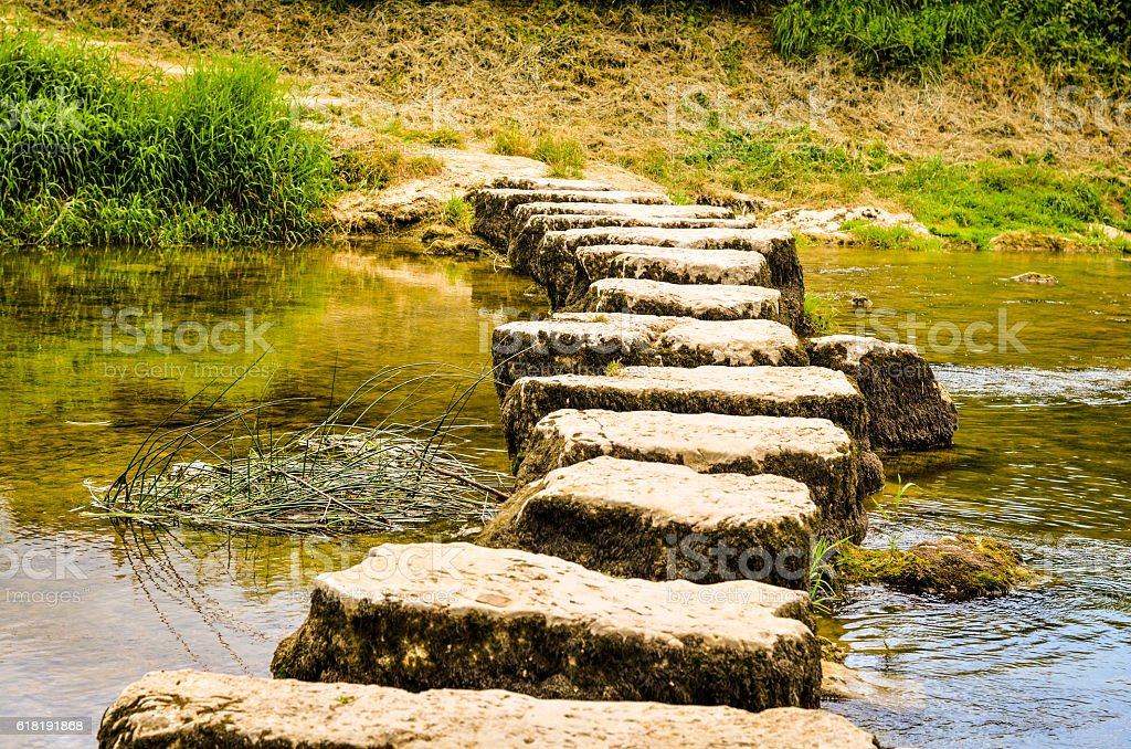stepping stones crossing a small river stock photo