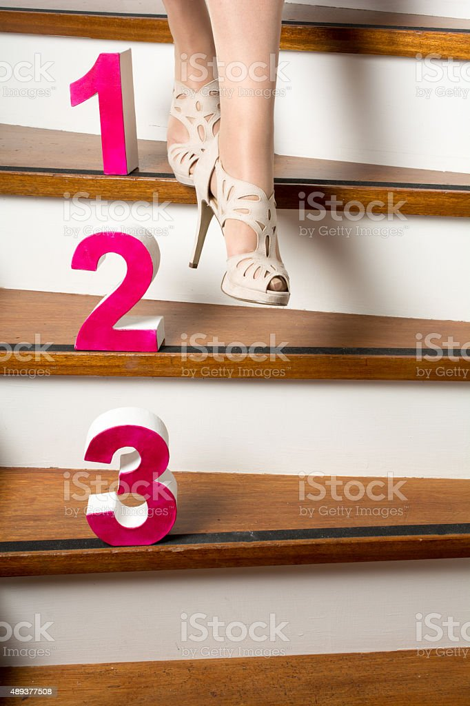 3 steps down the stairs with woman walking down stock photo